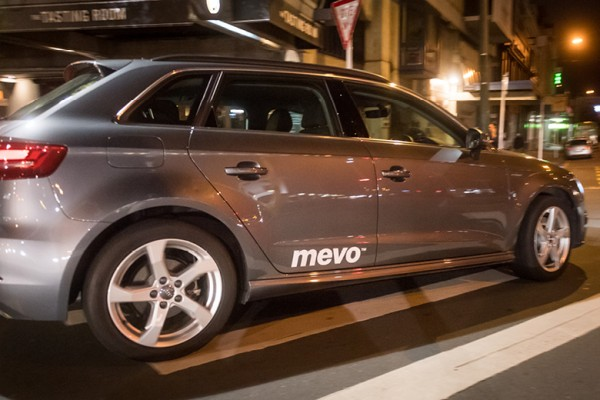 Image shows a Mevo car driving down a city street
